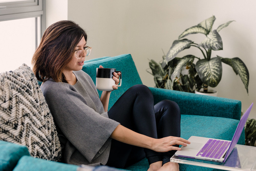 Rachel Off Duty: A Woman Sips Coffee While Working on a Blue Sofa