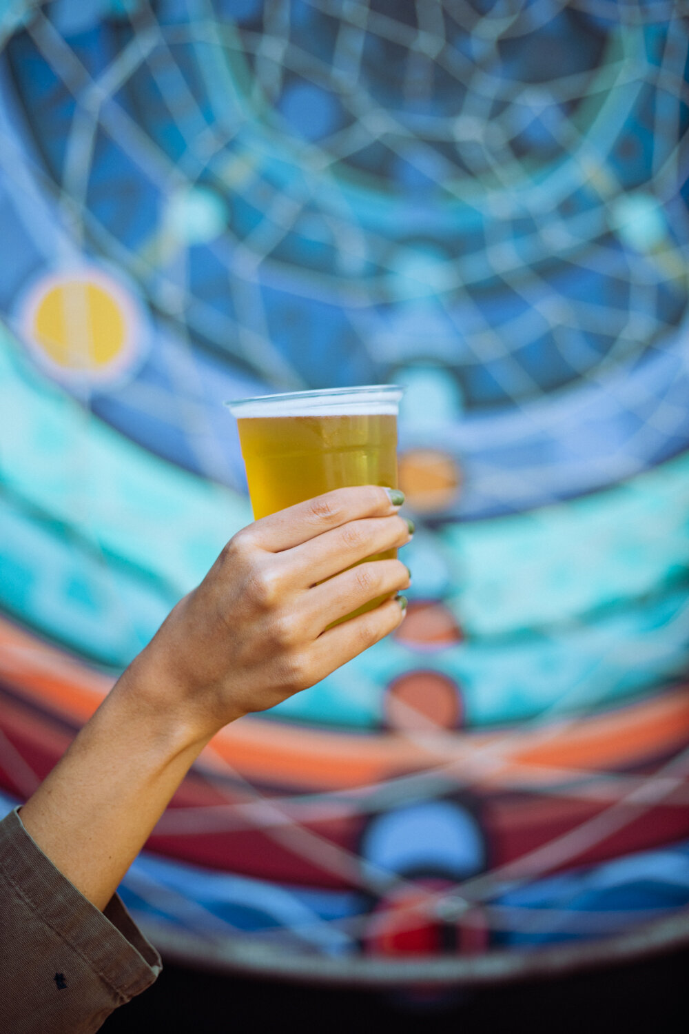 Rachel Off Duty: A Hand Holding a Light Beer in a Plastic Cup in front of a Blue Mural