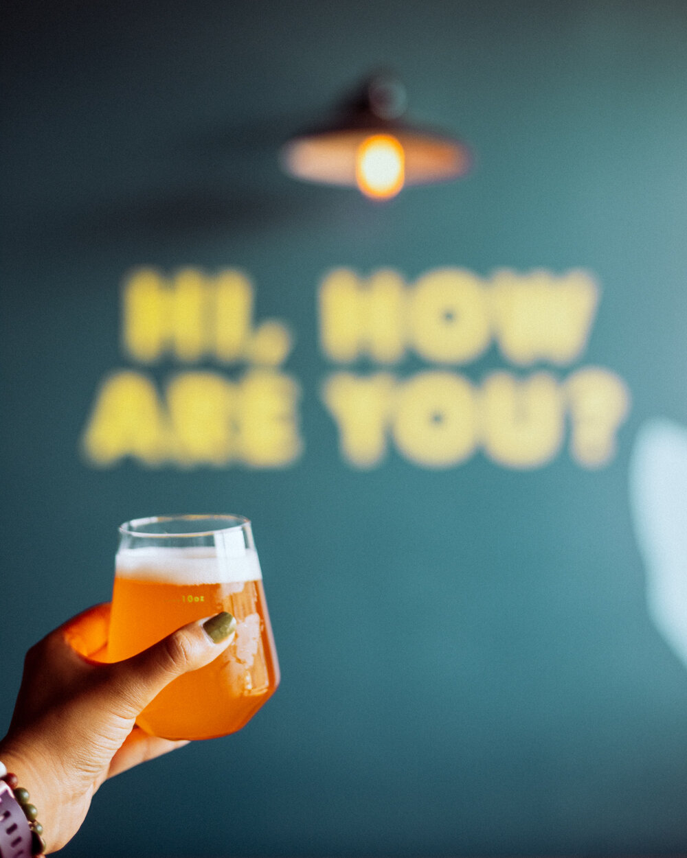 """Rachel Off Duty: A Hand Holding a Beer in front of a """"Hi, How Are You?"""" Mural"""