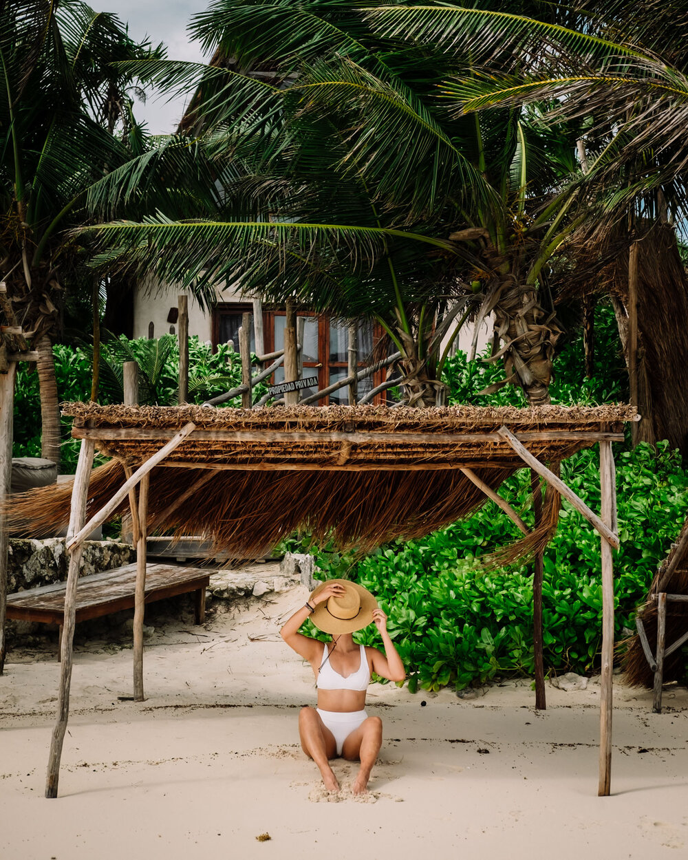 Rachel Off Duty: A Woman Covers Her Face with a Hat on a Beach in Tulum, Mexico