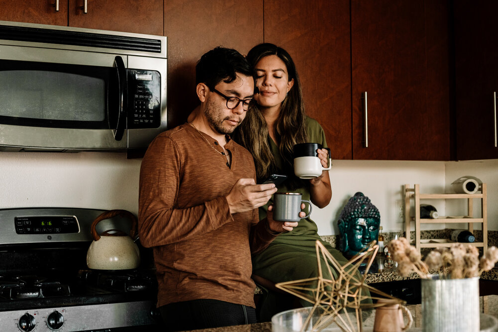 Rachel Off Duty: Man and Woman Drinking Coffee and Looking at Phone in Kitchen