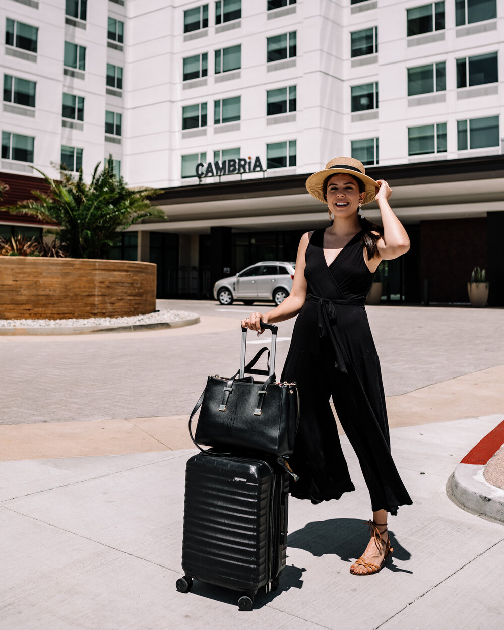 Rachel Off Duty: Woman in Black Jumpsuit with Luggage Standing in Front of Cambria Hotel in Anaheim