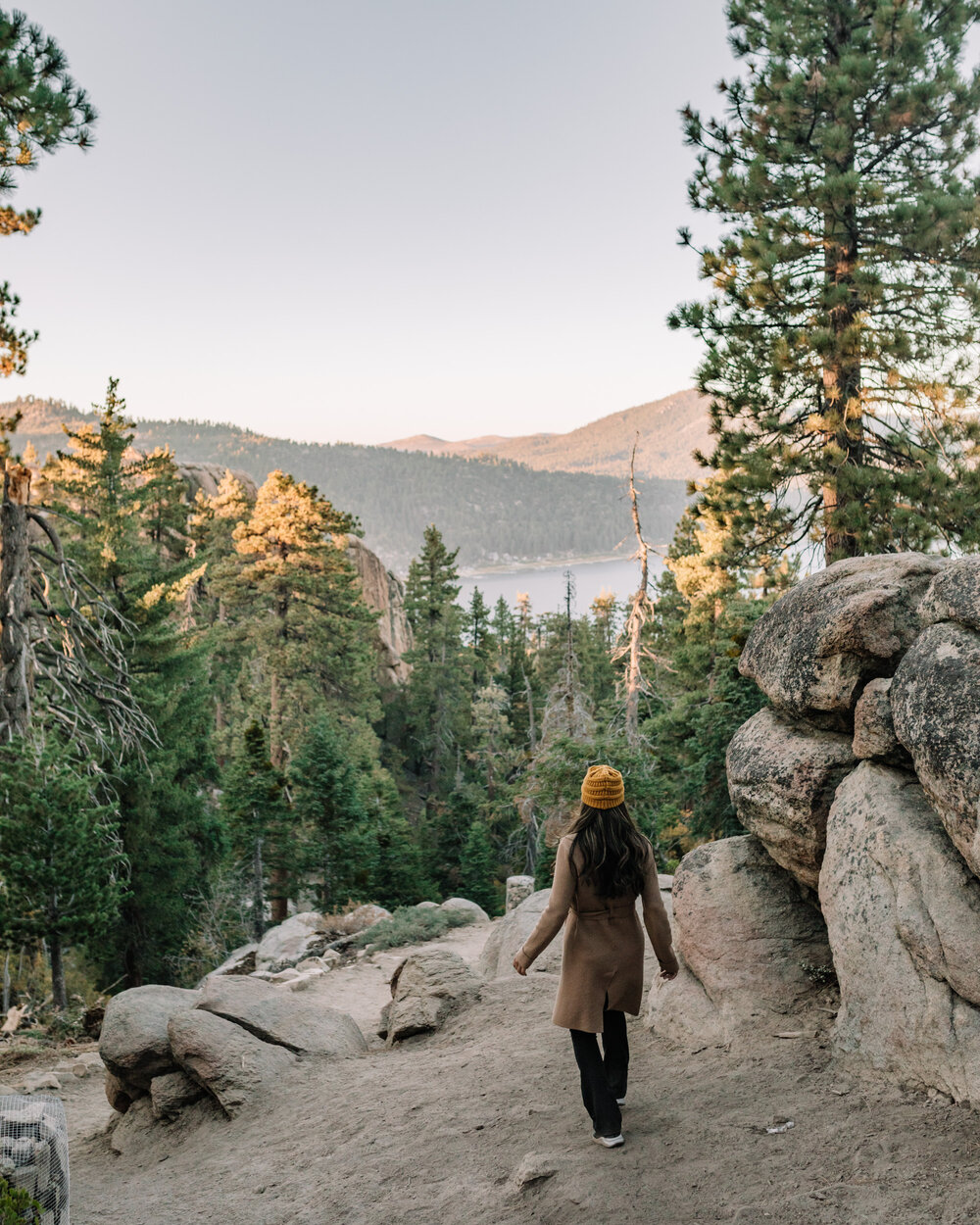 Rachel Off Duty: Woman in a coat hiking on a mountain with a view of a lake in Big Bear