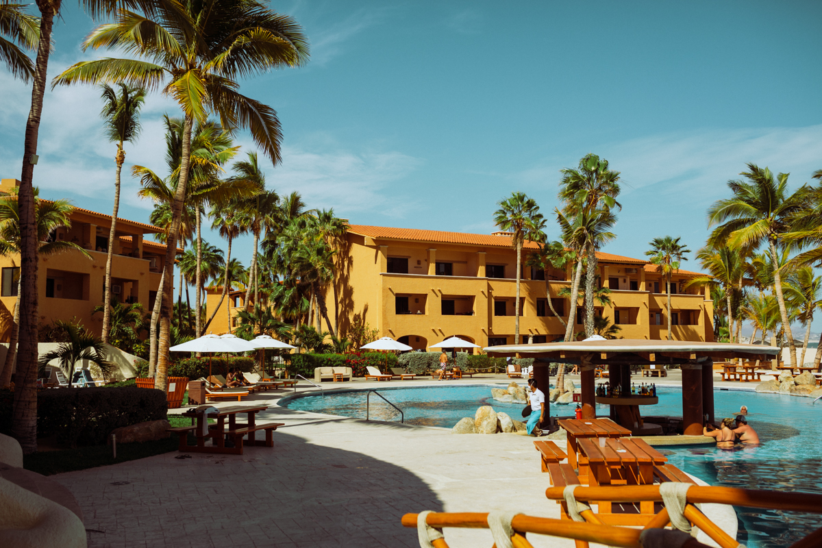Rachel Off Duty: A Hotel Pool and Swim-Up Bar Surrounded by Yellow Buildings and Palm Trees