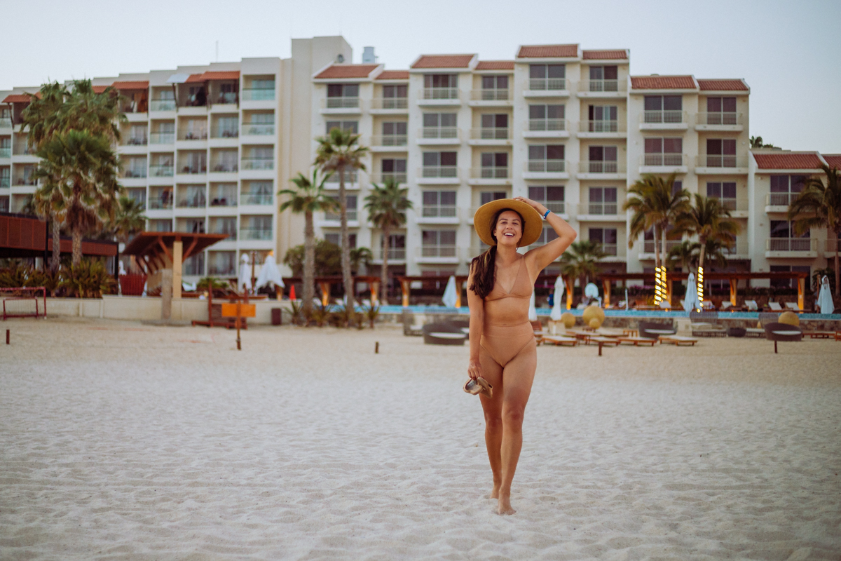 Rachel Off Duty: A girl in a swimsuit and hat smiles while walking on the beach in front of a resort
