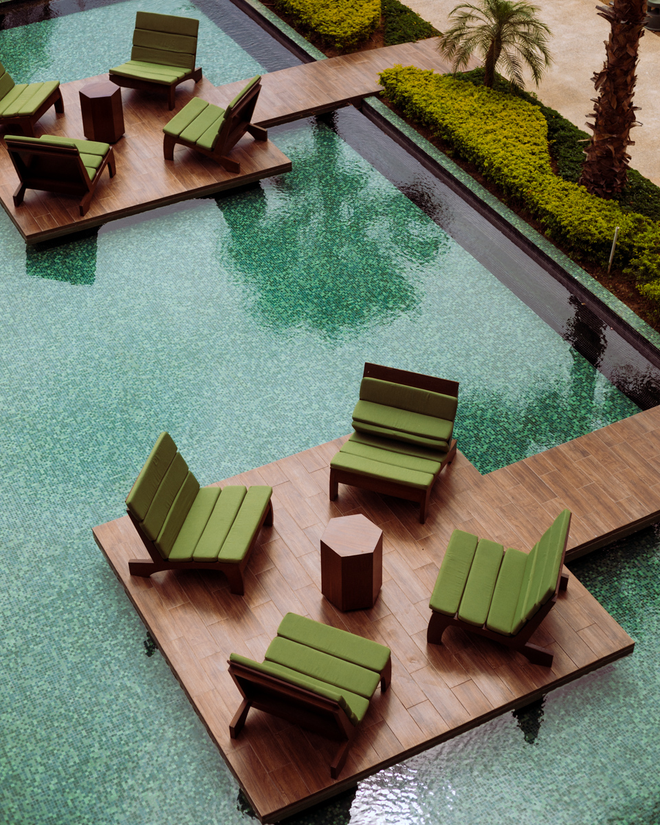 Rachel Off Duty: Green Chairs on a Wooden Platform Suspended Over a Water Fixture