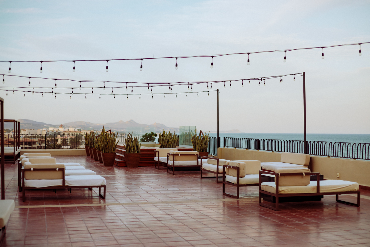 Rachel Off Duty: Rooftop Lounge With White Lounge Chairs Next to the Beach