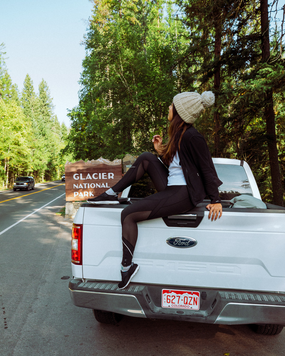 Rachel Off Duty: A Woman Sits in Front of the Glacier National Park Sign