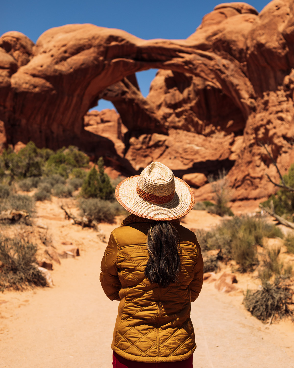 Rachel Off Duty: A Woman in a Yellow Jacket Admires the Double Arch in Arches National Park