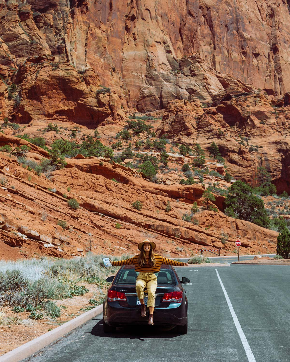Rachel Off Duty: A Woman Sits on the Back of a Sedan in a National Park Parking Lot