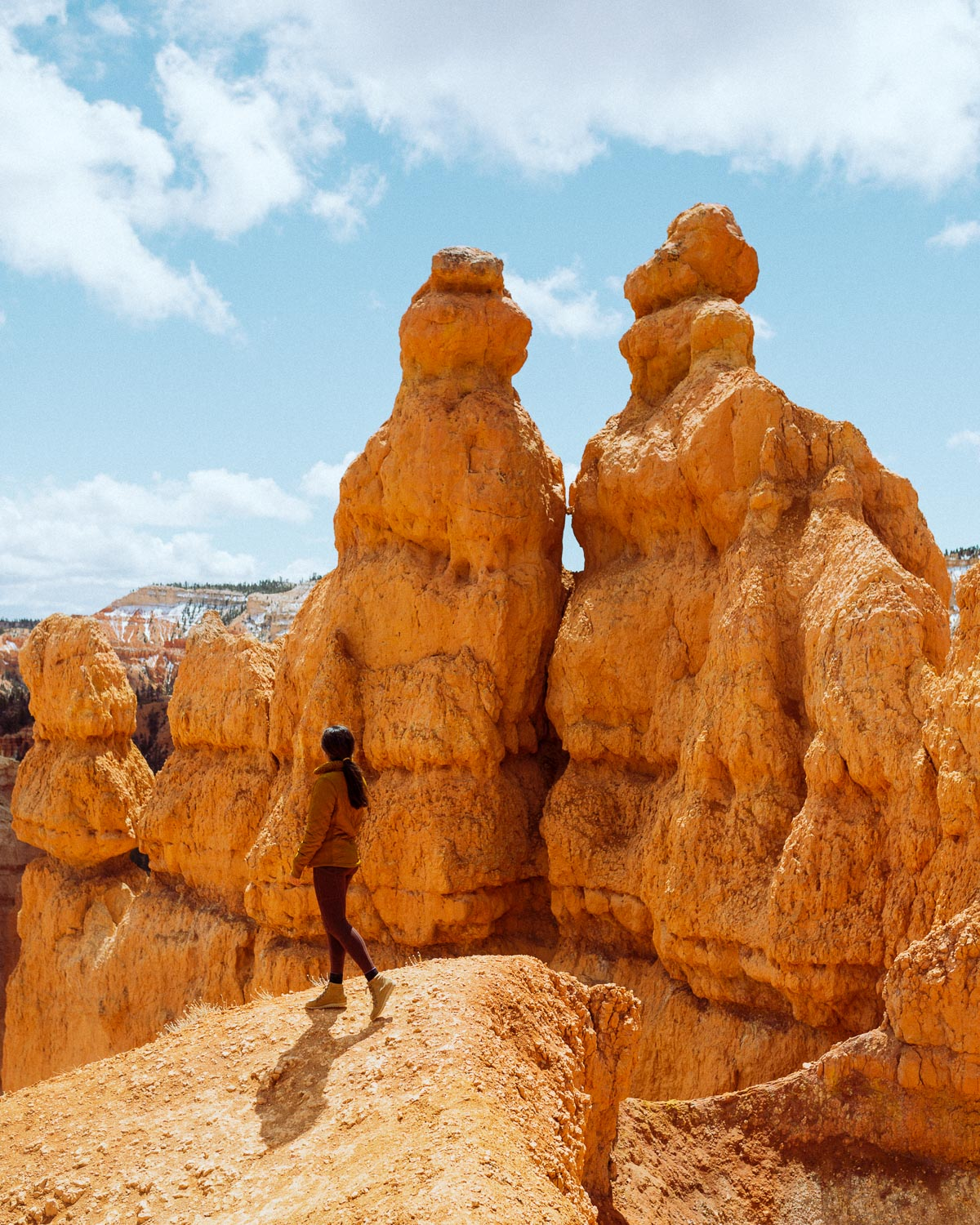 Rachel Off Duty: A Girl in a Yellow Jacket Stands Next to Hoodoos in Bryce Canyon