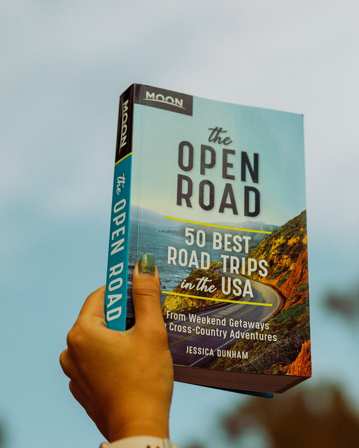 Rachel Off Duty: A Person Holds a Moon Travel Guides Road Trip Guidebook Up to the Sky